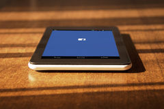 Facebook application on tablet. Tablet laying on the table with facebook page on the screen royalty free stock image