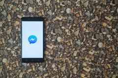 Facebook-Botelogo auf Smartphone auf Hintergrund von kleinen Steinen Lizenzfreies Stockbild
