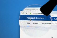 Facebook business homepage website on Apple iMac monitor screen under magnifying glass. Facebook is the most popular social Royalty Free Stock Images