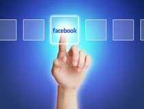 Facebook Concept. Hand press a button of facebook with blue gradually varied background Stock Photo