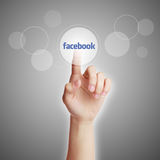 Facebook Concept. Hand press a button of facebook with gradually varied background Stock Photo
