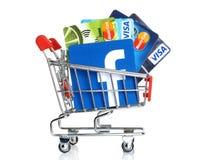 Facebook-embleem op papier wordt en in boodschappenwagentje met kaartenvisum en Mastercard op witte achtergrond wordt geplaatst g Stock Fotografie