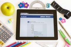 Facebook en Ipad 3 con los accesorios de la escuela Foto de archivo