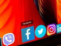 Facebook icon in dock of macbook on red background, close up. Social network stock photography