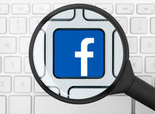 Facebook icon under the magnifying glass Royalty Free Stock Photos
