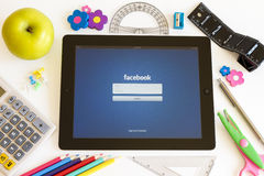 Facebook on Ipad 3 with school accesories. On white background Stock Photography