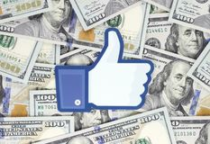 Facebook Like logo printed on paper, cut and placed on money background royalty free stock image