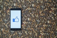 Facebook like logo on smartphone on background of small stones. Los Angeles, USA, october 18, 2017: Faceboook like logo on smartphone on background of small Royalty Free Stock Photo