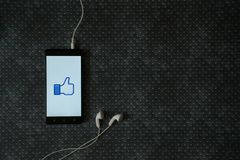 Facebook like logo on smartphone screen. Los Angeles, USA, october 23, 2017: Facebook like logo on smartphone screen and earphones plugged in on metal plate Royalty Free Stock Photos
