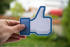 Facebook like. Printed on paper and holding Royalty Free Stock Image