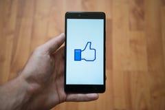 Facebook like thumb logo on smartphone screen. London, United Kingdom, june 5, 2017: Man holding smartphone with Facebook like thumb logo on the screen. Laminate Royalty Free Stock Photo
