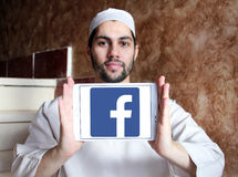 Facebook logo. Facebook application logo and vector on samsung tablet holded by arab muslim man Royalty Free Stock Images