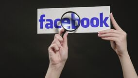 Facebook logo hand spying website magnifying glass