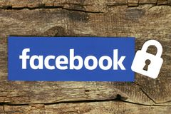 Facebook logo with lock placed on old wooden background Stock Images