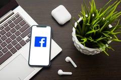 Facebook logo na iphone X ekranie umieszcza na laptop klawiaturze obok AirPods obraz stock