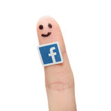 Facebook logo printed on paper and stuck to the finger. Royalty Free Stock Photo