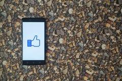 Facebook mögen Logo auf Smartphone auf Hintergrund von kleinen Steinen Lizenzfreies Stockfoto