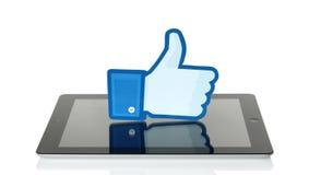 Facebook manosea con los dedos encima de la muestra impresa en el papel y puesta en iPad en el fondo blanco Fotos de archivo