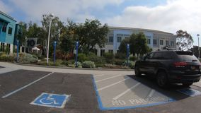 Facebook Menlo Park. Menlo Park, California, United States - August 13, 2018: Numbered seats for employees car in front of the colorful buildings of Facebook stock footage