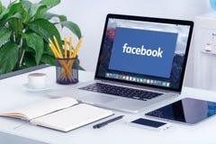 Facebook ny logo på den Apple MacBook Pro skärmen royaltyfri bild
