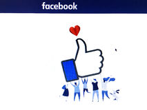 Facebook page with people figures carry a like sign. Stock Image