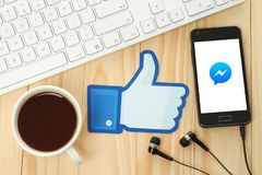 Facebook sfoglia sul segno stampato su carta e disposto sulle sedere di legno Immagini Stock