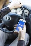 Facebook sur le mobile dans la voiture tout en conduisant Images libres de droits