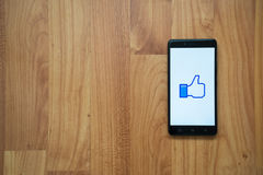 Facebook Thumb up like on smartphone. Los Angeles, USA, july 13, 2017: Facebook Thumb up like logo on smartphone screen on wooden background Stock Image