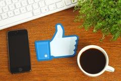 Facebook thumbs вверх по знаку помещенному на деревянной предпосылке с кофе, клавиатурой и умным телефоном Стоковые Фотографии RF
