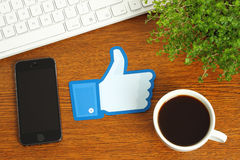 Facebook thumbs up sign placed on wooden background with coffee, keyboard and smart phone. KIEV, UKRAINE - MARCH 07, 2015: Facebook thumbs up sign printed on royalty free stock photos