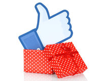 Facebook thumbs up sign into present box. Kiev, Ukraine - January 11, 2016: Facebook thumbs up sign printed on paper and put into present box on white background Royalty Free Stock Image