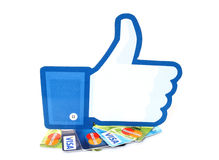 Facebook thumbs up sign printed on paper and placed on cards Visa and MasterCard on white background Stock Photos