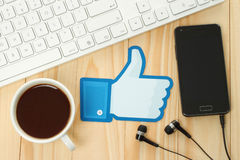 Facebook thumbs up sign printed on paper and placed on wooden background Royalty Free Stock Photos