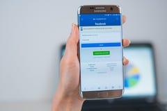 Facebook webbplats som ?ppnas p? mobilen royaltyfri fotografi