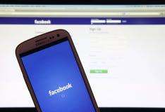 Facebook-webpagina op smartphone en laptop Stock Foto