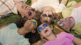 Faceci i dziewczyny ogląda śmiesznego wideo na telefonie podczas gdy kłamający na trawie, szczęście zdjęcie wideo