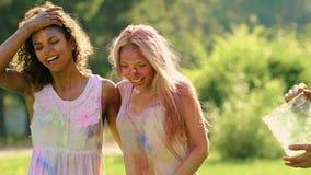 Faceci nalewa barwiącą wodę na dziewczynach, z podnieceniem przyjaciele ma zabawę przy Holi przyjęciem zbiory