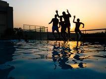 Faceci skacze w wodę z zmierzchem zdjęcia stock