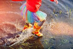 Girl in gumboots splashing spring puddle. Faceless active girl in colorful outfit and gumboots running in water of puddle having fun in sunset Royalty Free Stock Photo