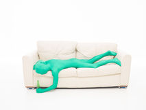 Faceless green man felt on coutch. Faceless man dressed in green suit fell on the couch with a beer in hand Royalty Free Stock Image
