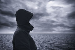 Faceless hooded person looking at horizon over sea water Royalty Free Stock Photos