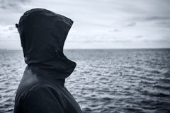 Faceless hooded person looking at horizon over sea water Stock Image