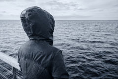 Faceless hooded person looking at horizon over sea water Royalty Free Stock Images
