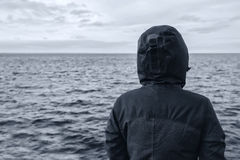 Faceless hooded person looking at horizon over sea water Royalty Free Stock Photo