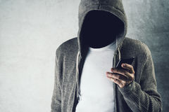 Faceless hooded person using mobile phone, identity theft concep Stock Photo
