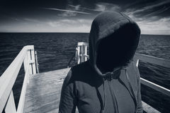 Faceless Hooded Unrecognizable Woman at Ocean Pier, Abduction Co. Abduction Concept, Faceless Hooded Unrecognizable Woman at Ocean Pier, Unknown Spooky Female Royalty Free Stock Image