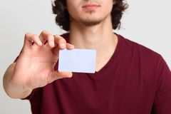Faceless male stretches hand with blank card for your advertisement or promotion text, poses at white background, man wearing. Maroon t shirt. Online shopping stock images