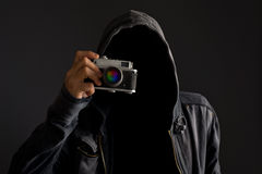 Faceless man with dusty camera. Faceless man with hoodie jacket holding dusty vintage film camera and taking photographs stock photography