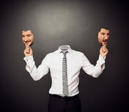 Faceless man holding masks Royalty Free Stock Photos