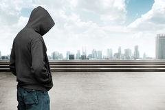 Faceless man in hood. With cityscape background royalty free stock image
